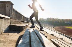 Chiuda su della donna che corre di sopra sullo stadio Fotografie Stock Libere da Diritti