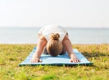 Chiuda su della donna che fa gli esercizi di yoga all'aperto Fotografie Stock
