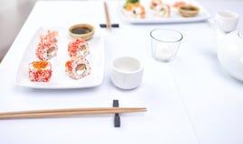 Chiuda su della donna che mangia i sushi al ristorante Fotografia Stock