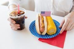 Chiuda su della donna che mangia il hot dog con coca-cola Immagini Stock
