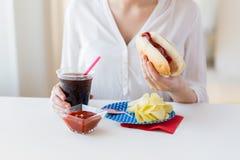 Chiuda su della donna che mangia il hot dog con coca-cola Fotografia Stock