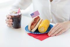 Chiuda su della donna che mangia il hot dog con coca-cola Immagine Stock