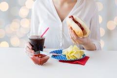 Chiuda su della donna che mangia il hot dog con coca-cola Fotografie Stock Libere da Diritti
