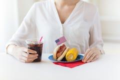 Chiuda su della donna che mangia il hot dog con coca-cola Immagini Stock Libere da Diritti