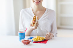 Chiuda su della donna che mangia l'hot dog e le patate fritte Immagini Stock Libere da Diritti