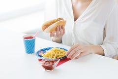 Chiuda su della donna che mangia l'hot dog e le patate fritte Immagine Stock