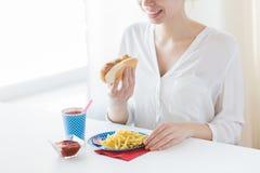 Chiuda su della donna che mangia l'hot dog e le patate fritte Fotografia Stock
