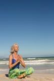 Chiuda su della donna che medita mentre si siedono sulla riva contro il chiaro cielo Immagini Stock Libere da Diritti