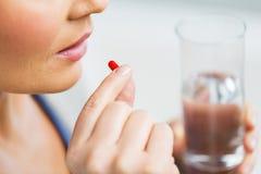 Chiuda su della donna che prende la medicina in pillola Fotografia Stock