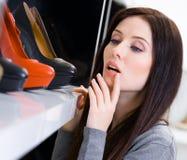 Chiuda su della donna che sceglie un paio delle scarpe immagini stock