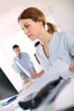 Chiuda su della donna che si siede nell'ufficio con il computer Fotografie Stock