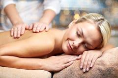 Chiuda su della donna che si trova e che ha massaggio in stazione termale Immagini Stock