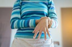 Chiuda su della donna che soffre con i sintomi del morbo di parkinson, paziente femminile della mano con stringere la mano immagini stock