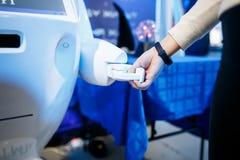 Chiuda su della donna che stringe le mani con un robot Fotografia Stock