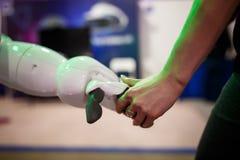 Chiuda su della donna che stringe le mani con un robot Immagini Stock Libere da Diritti