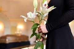 Chiuda su della donna con i fiori del giglio al funerale fotografia stock