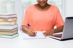 Chiuda su della donna con il computer portatile ed i libri a casa Fotografia Stock