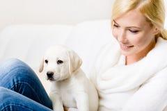 Chiuda su della donna con il cucciolo sulle sue ginocchia fotografia stock