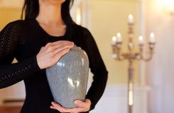 Chiuda su della donna con l'urna di cremazione in chiesa immagine stock libera da diritti