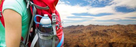 Chiuda su della donna con la bottiglia di acqua in zaino fotografia stock libera da diritti