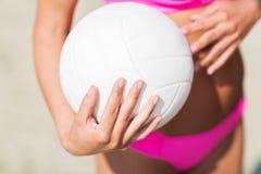 Chiuda su della donna con la palla di pallavolo sulla spiaggia Fotografie Stock