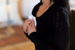 Chiuda su della donna con la strofinata al funerale in chiesa immagine stock