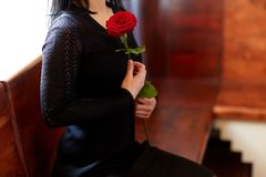 Chiuda su della donna con le rose al funerale in chiesa immagini stock libere da diritti