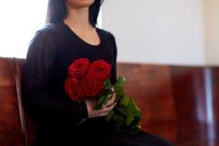 Chiuda su della donna con le rose al funerale in chiesa immagini stock
