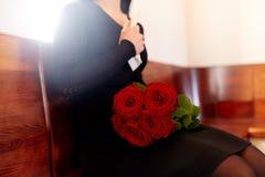 Chiuda su della donna con le rose al funerale in chiesa immagine stock