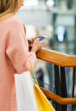 Chiuda su della donna con lo smartphone ed il sacchetto della spesa Immagini Stock Libere da Diritti