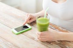 Chiuda su della donna con lo smartphone ed il succo verde Fotografia Stock Libera da Diritti