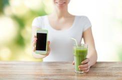 Chiuda su della donna con lo smartphone ed il succo verde Immagini Stock