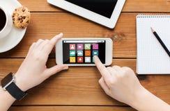 Chiuda su della donna con lo smartphone sulla tavola di legno Fotografia Stock