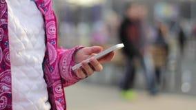 Chiuda su della donna delle mani che per mezzo del suo telefono cellulare archivi video