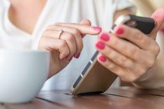 Chiuda su della donna delle mani che utilizza il suo telefono cellulare nel ristorante Fotografia Stock