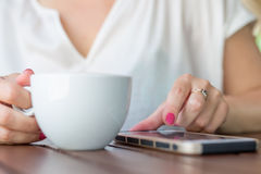 Chiuda su della donna delle mani che utilizza il suo telefono cellulare nel ristorante Immagine Stock Libera da Diritti