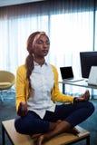 Chiuda su della donna di affari che fa l'yoga Fotografia Stock