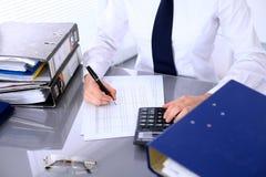 Chiuda su della donna di affari che stendere il rapporto, calcolatrice o controllante l'equilibrio Immagine Stock
