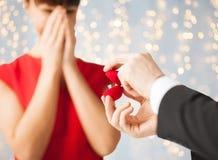 Chiuda su della donna e dell'uomo con l'anello di fidanzamento Fotografia Stock