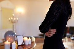 Chiuda su della donna e dell'urna di cremazione in chiesa immagini stock libere da diritti