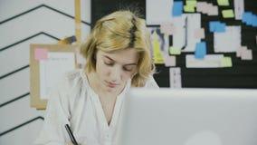 Chiuda su della donna europea che prende le note in blocco note facendo uso della penna all'ufficio moderno stock footage