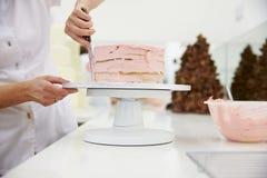 Chiuda su della donna in forno che decora il dolce con glassa immagine stock libera da diritti