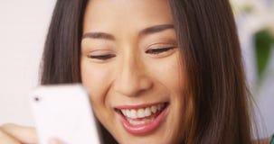 Chiuda su della donna giapponese che per mezzo dello smartphone immagine stock libera da diritti