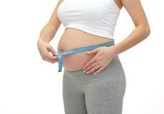 Chiuda su della donna incinta che misura la sua pancia Immagini Stock Libere da Diritti