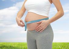 Chiuda su della donna incinta che misura la sua pancia Fotografie Stock Libere da Diritti