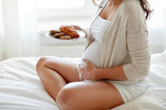 Chiuda su della donna incinta con i croissant a casa Immagini Stock Libere da Diritti