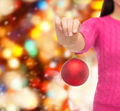 Chiuda su della donna in maglione con la palla di natale Fotografia Stock