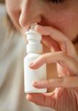 Chiuda su della donna malata che per mezzo dello spray nasale Fotografie Stock