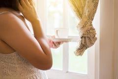 Chiuda su della donna della mano che tiene una tazza di caff? e che guarda qualcosa sulla finestra a casa di mattina immagini stock libere da diritti