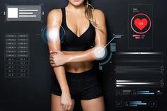 Chiuda su della donna nella posa nera degli abiti sportivi Immagine Stock